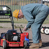 Dr. Bill Markel adds oil and gas to a lawnmower during the lawnmower clinic at the United Church of Broomfield on Saturday.<br /> April 2, 2011<br /> staff photo/David R. Jennings