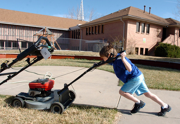 George Cheatham, 9, pushes a lawnmower to the cleaning area for the lawnmower clinic at the United Church of Broomfield on Saturday.<br /> April 2, 2011<br /> staff photo/David R. Jennings