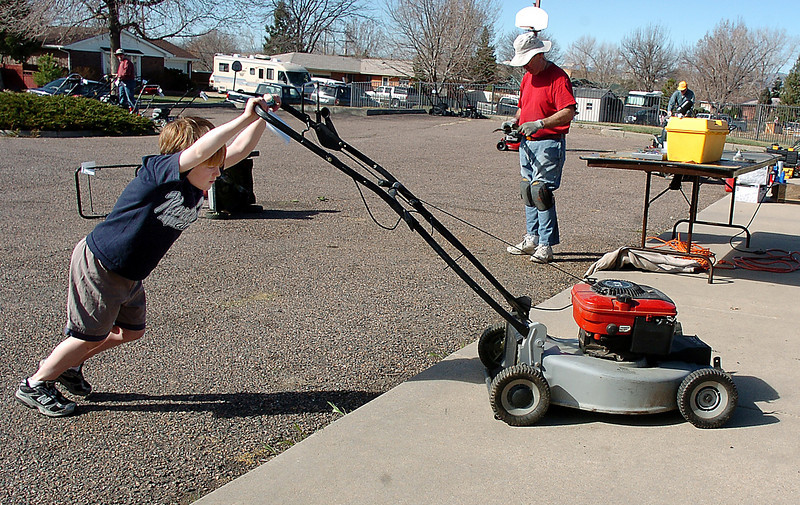 Jack Cheatham, 7, pushes a mower to the cleaning area after the blade was removed during the lawnmower clinic at the United Church of Broomfield on Saturday.<br /> April 2, 2011<br /> staff photo/David R. Jennings
