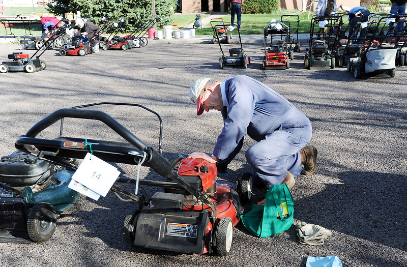 Dr. Bill Markel changes a spark plug on a lawnmower during the United Church of Broomfield 17th annual Lawnmower Clinic on Saturday.<br /> <br /> <br /> April 14, 2012 <br /> staff photo/ David R. Jennings