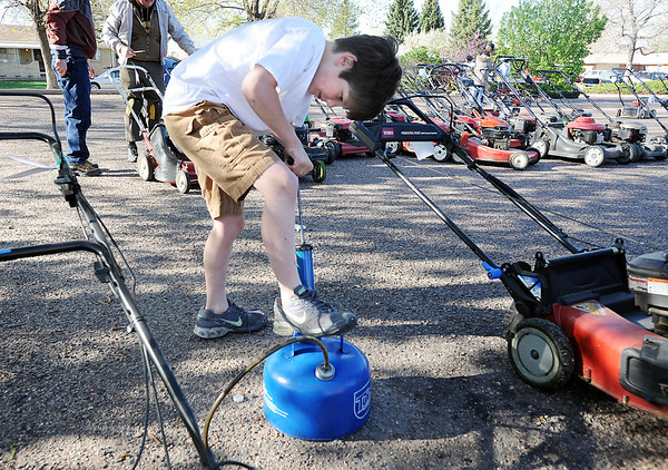 George cheatham, 10, siphons old gas from a lawnmower during the United Church of Broomfield 17th annual Lawnmower Clinic on Saturday.<br /> <br /> <br /> <br /> April 14, 2012 <br /> staff photo/ David R. Jennings