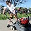 George Cheatham, 10, tips a lawnmower over so he can scrap off grass during the United Church of Broomfield 17th annual Lawnmower Clinic on Saturday.<br /> <br /> <br /> <br /> April 14, 2012 <br /> staff photo/ David R. Jennings