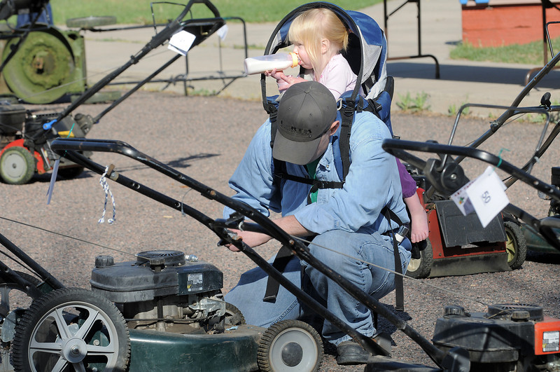 Seth Cheatham works on a lawnmower while his 18 month old daughter, Jude, drinks her milk during the United Church of Broomfield 17th annual Lawnmower Clinic on Saturday.<br /> t<br /> <br /> April 14, 2012 <br /> staff photo/ David R. Jennings