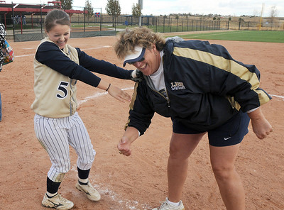 Legacy's Payton Price, left, has a laugh with coach Dawn Gaffin after winning their third state 5A softball championship by  defeating Ralston Valley 1-0 in 8 innings, Saturday, at the Aurora Sports Park.  October 24, 2009 Staff photo/David R. Jennings