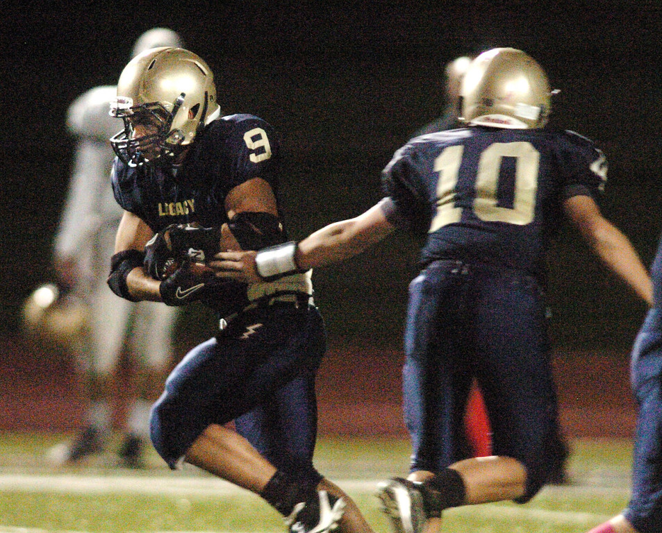 Dezmon Fernandez takes the ball from Legacy's quarterback Steven Yoshihara during Thursday's game against Boulder at North Stadium.<br /> <br /> October 14, 2010<br /> staff photo/David R. Jennings