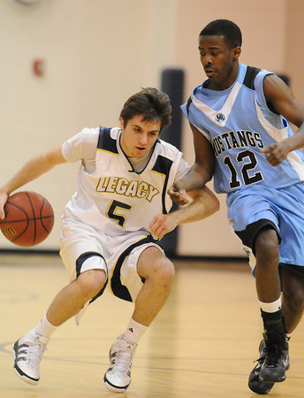 Legacy's Justin Walters dribbles the ball around  Mountain Range's Taylor Maunu during Tuesday's game at Legacy.<br /> <br /> <br /> February 9, 2010<br /> Staff photo/David R. Jennings