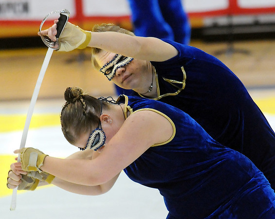 Kourtney Bernhardt passes a sword to Jeff Martin during Legacy's Color Guard performance at the Rocky Mountain Color Guard Association state competition at Legacy  on Saturday.<br /> <br /> March 27, 2010<br /> Staff photo/David R. Jennings