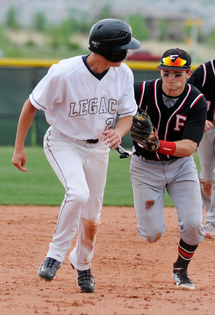 Fairview's Cameron Frazier chases Legacy's Jacob Camerlo to tag him out after Camerlo was caught between second and third bases during Thursday's game at Legacy.<br /> <br /> April 26, 2012 <br /> staff photo/ David R. Jennings