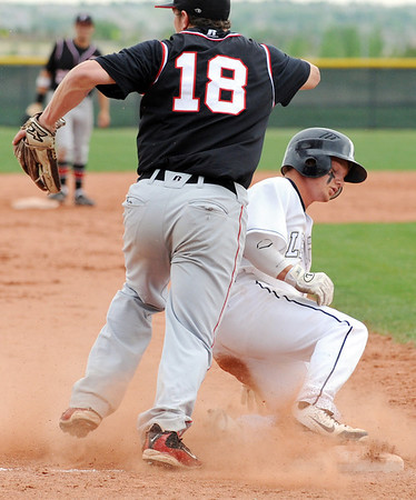 Legacy's Dillon Bollig safely slides to thirdbase past  Fairview's Jack Madden during Thursday's game at Legacy.<br /> <br /> April 26, 2012 <br /> staff photo/ David R. Jennings