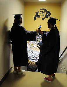 Two graduates share a cell phone photo while waiting for  Wednesday's 10th Legacy HIgh School graduation at Coors Events Center at CU. May 19, 2010 Staff photo/ David R. Jennings