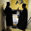 Two graduates share a cell phone photo while waiting for  Wednesday's 10th Legacy HIgh School graduation at Coors Events Center at CU.<br /> May 19, 2010<br /> Staff photo/ David R. Jennings