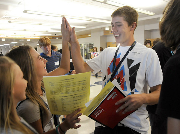 Paige Reichmuth, left, gives a high five to Patrick Medina after looking at their schedules during freshman orientation day at Legacy High School on Wednesday. <br /> <br /> August 19, 2009<br /> staff photo/David R. Jennings