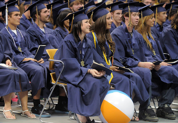 One of the few beach balls rests at the feet of a senior  after being tosses around during Legacy's graduation ceremony on Monday at Coors Event Center in Boulder.<br /> May 16, 2011<br /> staff photo/David R. Jennings