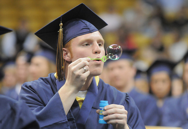 Christian Parks blows bubbles during the presentation of diplomas at Legacy's graduation on Monday at Coors Event Center in Boulder.<br /> May 16, 2011<br /> staff photo/David R. Jennings