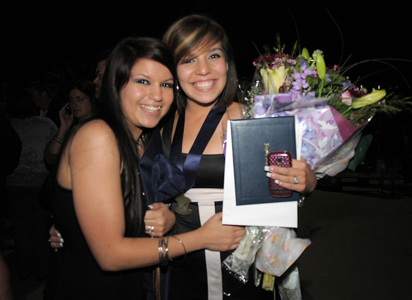 Lexi Lopez, left, and D'Niece Martinez smile for the camera in the dark after Legacy's graduation on Monday at Coors Event Center in Boulder.<br /> May 16, 2011<br /> staff photo/David R. Jennings