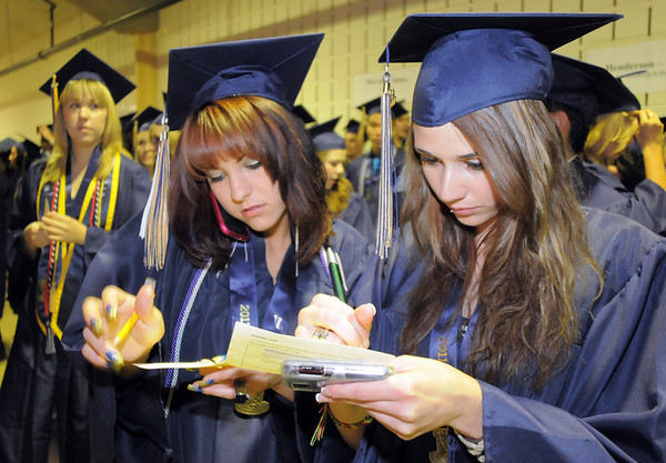 Tasia Hine, left, and Britany Henderson fill out forms before Legacy High's graduation on Monday at Coors Event Center in Boulder.<br /> May 16, 2011<br /> staff photo/David R. Jennings