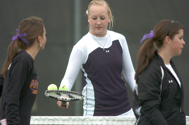 Legacy's Molly Madisen, center, exchanges tennis balls with Holy Family's Mary Caldwell and Madi Gosselin,  during the #1 doubles match at Legacy on Wednesday.<br /> <br /> March 31, 2010<br /> Staff photo/David R. Jennings