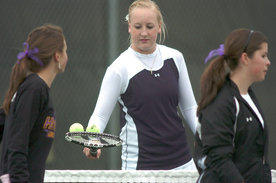 Legacy's Molly Madisen, center, exchanges tennis balls with Holy Family's Mary Caldwell and Madi Gosselin,  during the #1 doubles match at Legacy on Wednesday.  March 31, 2010 Staff photo/David R. Jennings