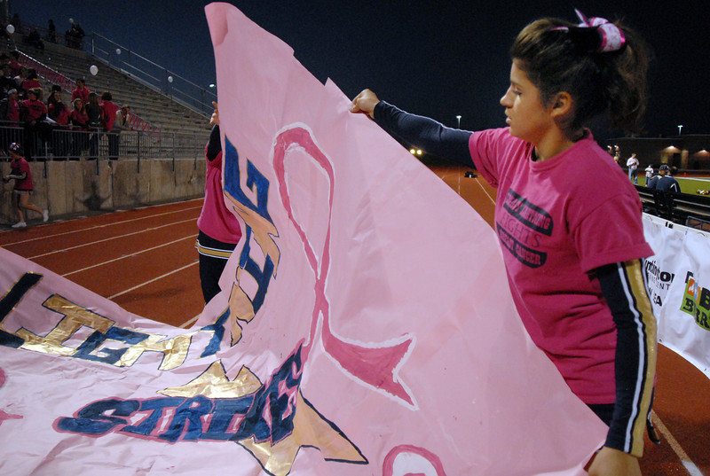 Legacy cheerleader Megan Gioia unfolds a pink banner for Thursday's Pink Out football game at North Stadium. The cheerleaders sold pink t-shirts, blankets and had a raffle for a pink Schwinn bicycle to raise money for breast cancer research.<br /> <br /> October 14, 2010<br /> staff photo/David R. Jennings