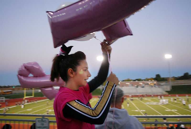 Legacy cheerleader Cynthia Ruvalcaba carries a pink ribbon balloon  for display at Thursday's Pink Out football game at North Stadium. The cheerleaders sold pink t-shirts, blankets and had a raffle for a pink Schwinn bicycle to raise money for breast cancer research.<br /> <br /> October 14, 2010<br /> staff photo/David R. Jennings