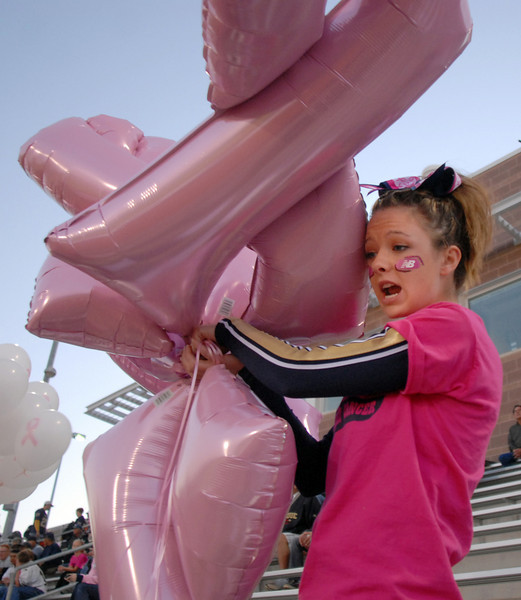 Legacy cheerleader Alex Vandeboogaard holds pink ribbon balloons for display for Thursday's Pink Out football game at North Stadium. The cheerleaders sold pink t-shirts, blankets and a raffle for a pink Schwinn bicycle to raise money for breast cancer research.<br /> <br /> October 14, 2010<br /> staff photo/David R. Jennings