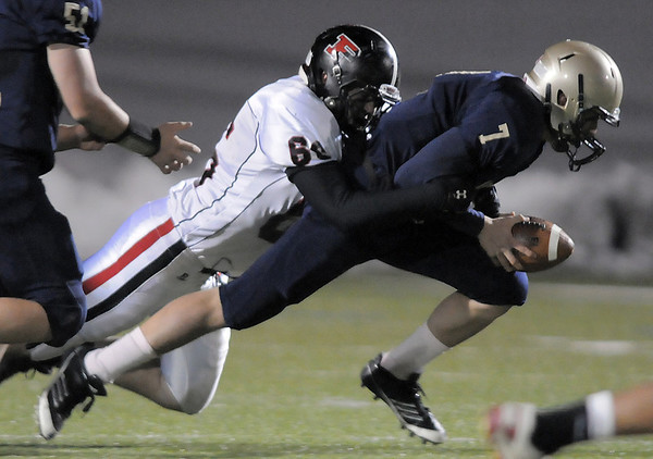 After scooping up a fumble Legacy's quarterback Patrick Medina is tackled by Pomona's Kenny Shinley during Thursday's game at North Stadium.<br /> October 27, 2011<br /> staff photo/ David R. Jennings