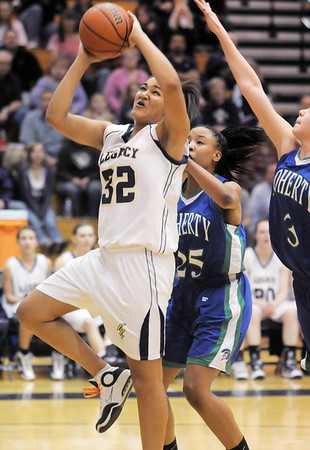 Legacy's Sade Akindele goes to the basket past Aiesha Harris and Kimberly Cerjan, Doherty during Tuesday's state 5A playoff game at Legacy.<br /> <br /> March 1, 2011<br /> staff photo/David R. Jennings