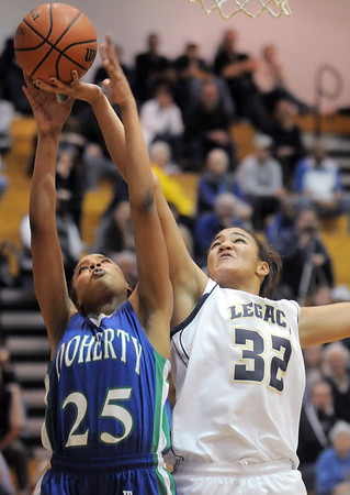 Legacy's Sade Akindele goes to the basket against Aiesha Harris, Doherty during Tuesday's state 5A playoff game at Legacy.<br /> <br /> March 1, 2011<br /> staff photo/David R. Jennings