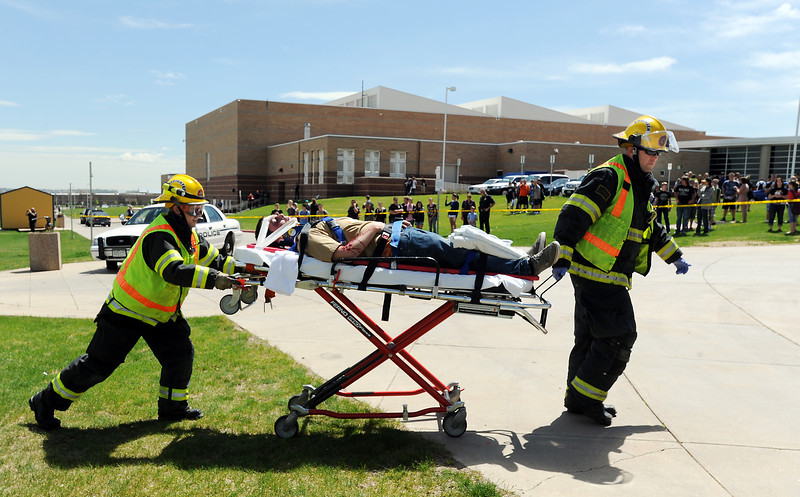 Legacy student volunteer Sam Thomas is carried to an ambulance by North Metro Fire Rescue District paramedic Eric Farnsworth, left, and engineer Don Woodmansee during the pre-prom drunk driving mock accident demonstration at Legacy High School on Thursday.<br /> <br /> April 26, 2012 <br /> staff photo/ David R. Jennings