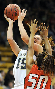 Legacy's Carli Moreland fights to the basket against Denver East's Tasha Carey during the class 5A championship game at the Coors Events Center in Boulder on Friday.   March 10, 2010 Staff photo/David R. Jennings