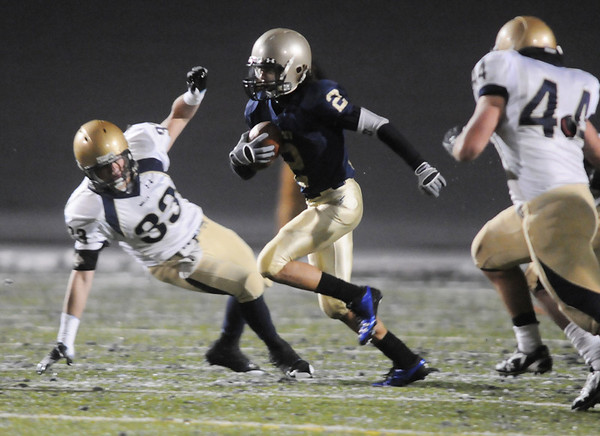 Cameron McWee, Legacy runs past Cole Gilmore and Hunter Foraker, Mullen during Friday's game at North Stadium.<br /> <br /> November 13, 2009<br /> Staff photo/David R. Jennings