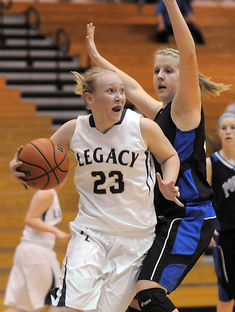 """Legacy's Caitlyn Smith drives the ball around Poudre's Ashley McDaniel during Thursday's game at Legacy. <br /> For more photos please see  <a href=""""http://www.broomfieldenterprise.com"""">http://www.broomfieldenterprise.com</a><br /> January 26, 2012<br /> staff photo/ David R. Jennings"""