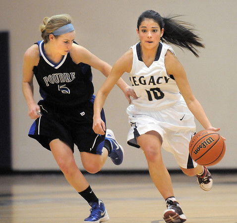 """Legacy's Emiley Lopez dribbles the ball downcourt against Poudre's Madison Hunt during Thursday's game at Legacy. <br /> For more photos please see  <a href=""""http://www.broomfieldenterprise.com"""">http://www.broomfieldenterprise.com</a><br /> January 26, 2012<br /> staff photo/ David R. Jennings"""
