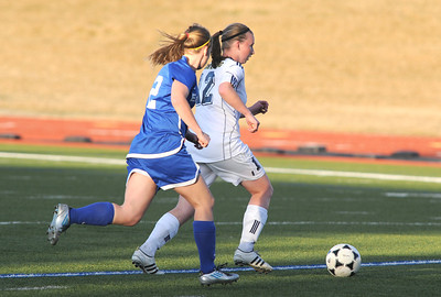Legacy's Sara Goodman advances the ball downfield past Broomfield's Katie Forsee during Thursday's game at North Stadium.  March 15,  2012  staff photo/ David R. Jennings
