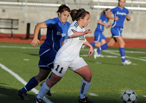 Legacy's Jesse Arellano moves the ball down field past  Broomfield's Kerri Marquardt during Thursday's game at North Stadium.<br /> <br /> March 15,  2012 <br /> staff photo/ David R. Jennings
