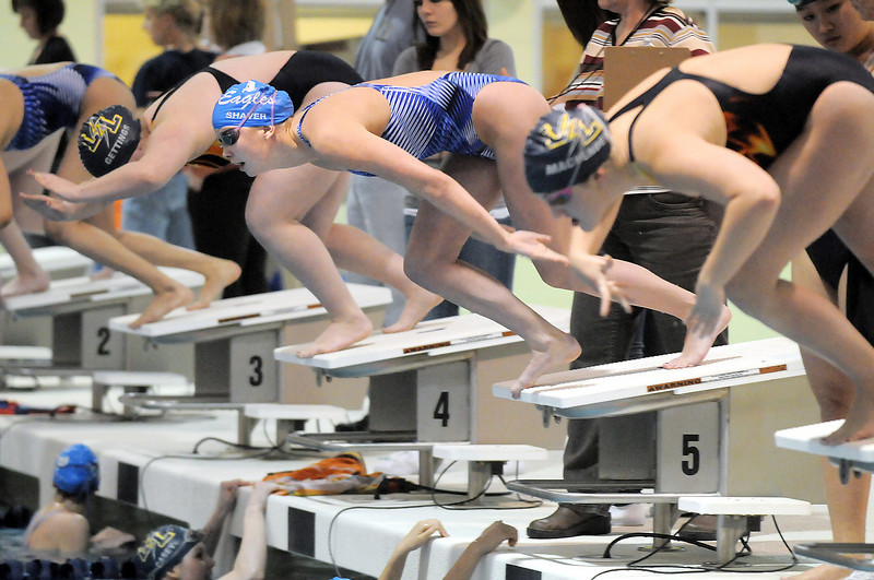 Broomfield's Heather Shaver, center, launches off the blocks for the 500 yard freestyle event during Tuesday's Legacy vs. Broomfield swim meet at the Veterans Memorial Aquatic Center in Thornton.<br /> <br /> January 25, 2011<br /> staff photo/David R. Jennings