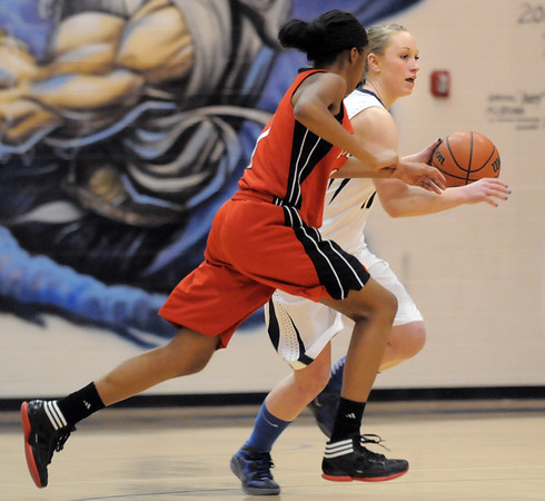 Legacy's Emily Glen drives the ball past Denver East's Ke'Avae Taylor during Wednesday's state 5A playoff game at Legacy.<br /> February 29, 2012 <br /> staff photo/ David R. Jennings