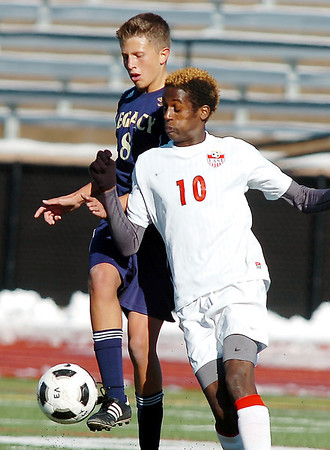 Legacy's Nick Smith kicks the ball away from Denver East's Ashi Gerkidane during the quarterfinals at Denver All City Stadium on Thursday.<br /> <br /> <br /> <br /> November 3, 2011<br /> staff photo/ David R. Jennings