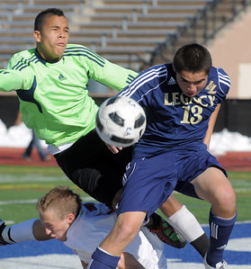 Legacy's Jacob Gonzales collides with Denver East's Tanner Drake and Ian Curtis at the goal during the quarterfinals at Denver All City Stadium on Thursday.    November 3, 2011 staff photo/ David R. Jennings
