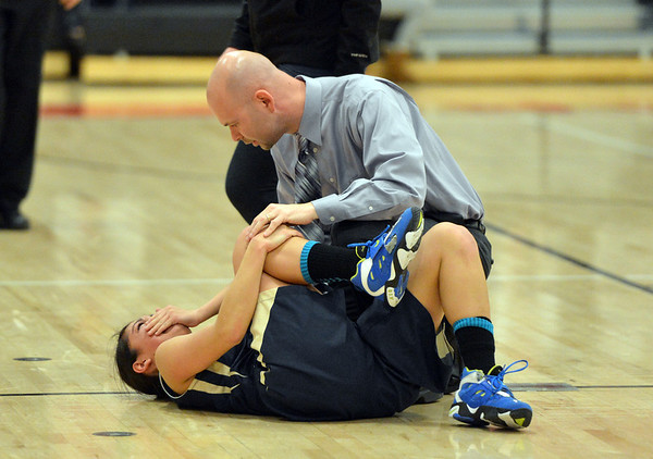 Legacy's head coach Craig Van Patten checks with Emiley Lopez holding her knee after she was injured during Friday's game against Denver East at Denver East.<br /> March 1, 2013<br /> staff photo/ David R. Jennings