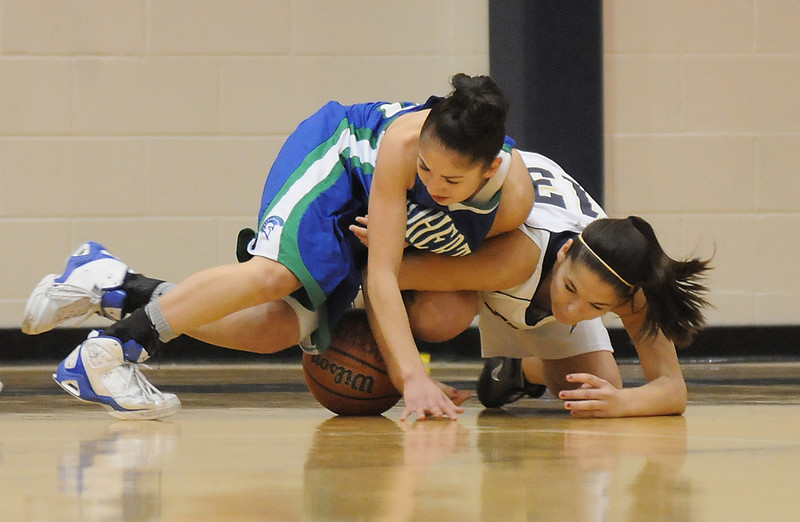 Legacy's Taylor Archuleta fghts for possession of the ball with Doherty's Angela Vigil during Saturday's state 5A playoff game at Legacy.<br /> February 27, 2010<br /> Staff photo/David R. Jennings