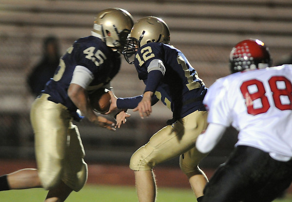 Legacy's quarterback Zach Hart hands off to Colton Chavez during Friday's game against Fairview  at 5 Star Stadium in Thornton.