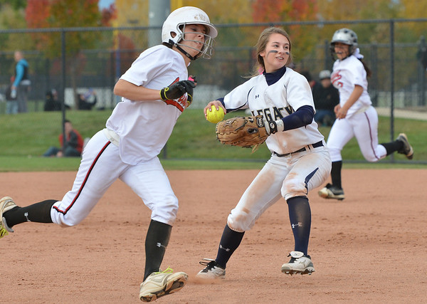 Legacy's Paige Reichmuth throws the ball while Loveland's Braydee Bakovich, left, and Maria Preciado round the bases during Saturday's state semi final 5A softball championship game at Aurora Sports Park.<br /> <br /> October 20, 2012<br /> staff photo/ David R. Jennings