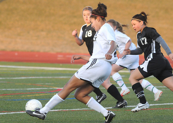 Legacy's Sade Akindele drives the ball past Carly Hillmer and Hannah Stimac, Monarch during Friday's game at North Stadium.<br /> <br /> April 9, 2010<br /> Staff photo/David R. Jennings