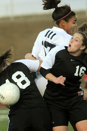 Legacy's Sade Akindele does a header past Monarch's Carly Hillmer. eft, and Kelsey Ftizgerald during Friday's game at North Stadium.<br /> <br /> April 9, 2010<br /> Staff photo/David R. Jennings