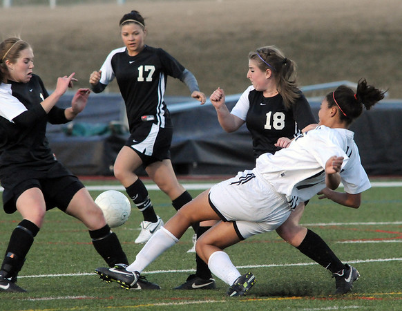 Legacy's Sade Akindele kicks the ball between three Monarch players during Friday's game at North Stadium.<br /> <br /> April 9, 2010<br /> Staff photo/David R. Jennings