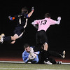 Legacy's keeper Christian Rivera, center,grabs the ball while Legacy's Tim Mooney, left, and  Mountain Range's Andrew Stauffer fall over Rivera during Tuesday's game at North Stadium.<br /> <br /> October 13, 2009<br /> Staff photo/David R. Jennings