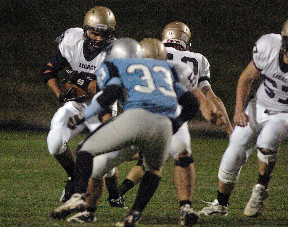 Legacy's Dezmon Fernandez carries the ball downfield around Justin Bralish, Ralston Valley, during Friday night's game at the North Area Athletic Complex in Arvada.<br /> October 8, 2010<br /> staff photo/David R. Jennings