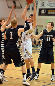 Legacy's Jesse Jacobsen catches the ball between of Fossil Ridge's Corey Peter and Evan Smith during Thursday's game at Legacy.  January 27, 2013 staff photo/ David R. Jennings
