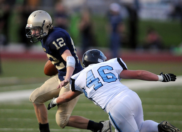 Legacy quarterback Bradie Koch tries to avoid a tackle by Bryce Dunkelberger, Mountain Range during Friday night's game at North Stadium.<br /> Sept. 3, 2009<br /> Staff photo/David R. Jennings